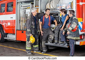 Firefighters Conversing By Firetruck - Team of smiling...