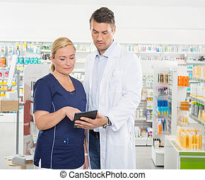 Assistant Using Tablet Computer With Pharmacist