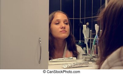 Young pretty woman washing face and brushing teeth in front of the mirror