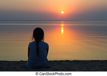 Girl at the sea at sunset