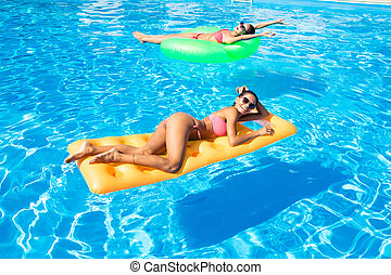 Two women lying on air mattress in the swimming pool -...