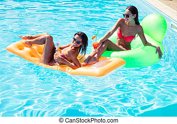 Girls resting on air mattress in swimming pool - Smiling two...