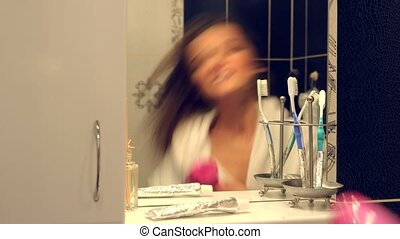 Happy beautiful young woman in a bathrobe singing and...