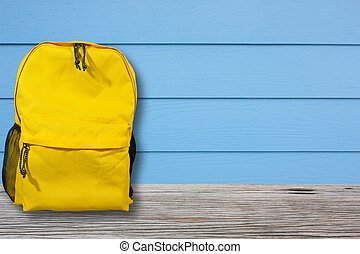 Bag or backpack is placed on a wooden table with blue walls.