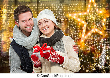 Happy young couple with Christmas present - Young man giving...