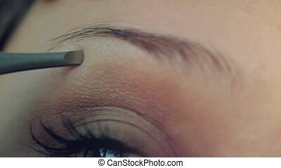 Young woman plucking eyebrows with tweezers close up. 4k