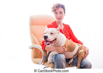 A girl holding a dog breed Staffordshire Terrier