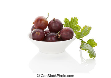 Red gooseberries - Red gooseberries in white bowl with green...