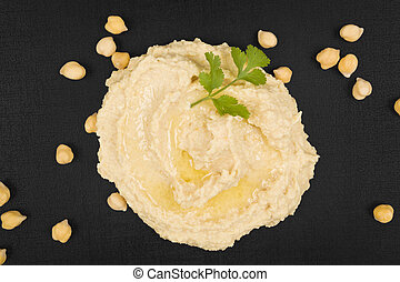 Hummus. - Hummus with parsley herb and chickpeas on black...
