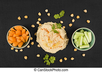 Delicious hummus background. Hummus, chickpeas, fresh carrot...