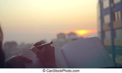 female hands with pen writing on notebook at sunset in the...