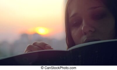 Young beautiful woman making some important notes on notebook at sunset in the city
