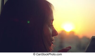 Young beautiful  woman using a smart phone at silhouette of city sunset