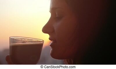 Slow motion of beautiful girl drinking coffee by the window at silhouette Of sunset City