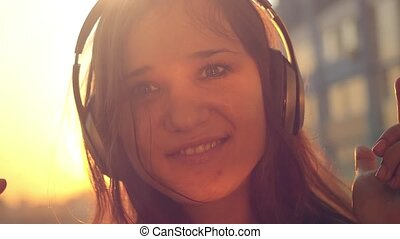 Slow motion of Young woman listening to music in headphones...