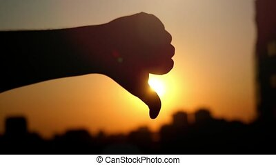Female hand showing a thumb down gesture at city sunset....