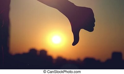 Female hand showing a thumb down gesture at city sunset...