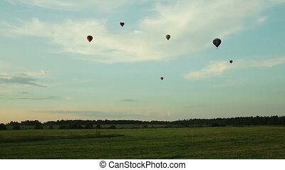 hot air balloons flying over field in countryside - Hot air...