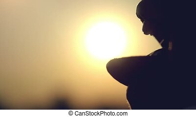 woman touches the sun and eats it by tongue at sunset time....