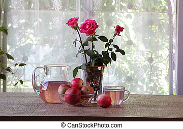 Compote from apples in a transparent jug on a wooden table -...