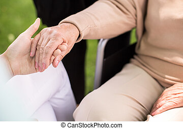 Nurse supporting disabled woman - Close-up of nurse...