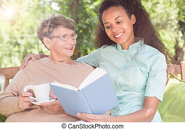 Reading book in the garden - Senior woman and caregiver...