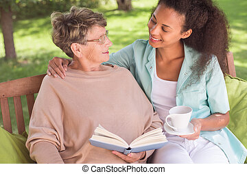 Senior and carer being friends - Senior woman and young...