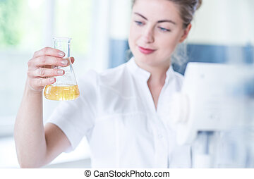 Worker of laboratory holding flask
