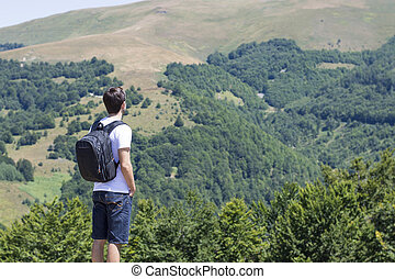 Young man with backpack standing on cliff's edge and looking to the mountains