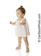 First Steps - An adorable baby girl nervously taking her...