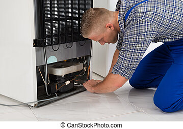 Repairman Making Refrigerator Appliance - Young Male...