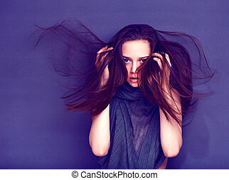 Fashion model with full lips and long hair poses on violet...
