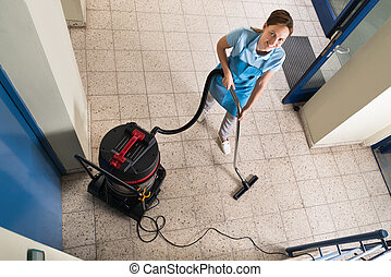 Janitor Vacuuming Floor - High Angle View Of Young Female...