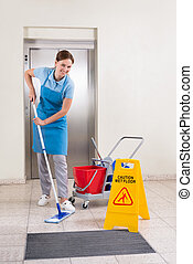 Worker With Cleaning Equipments And Wet Floor Sign - Young...