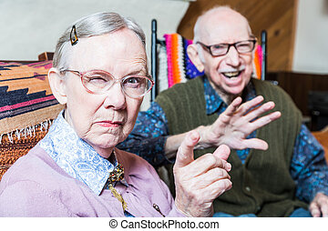 Angry Old Couple in Livingroom - Angry old couple sitting in...