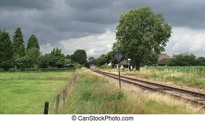 Steam train riding in countryside and whistles - on camera