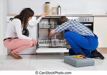 Woman Looking At Repairman Repairing Dishwasher - Young...