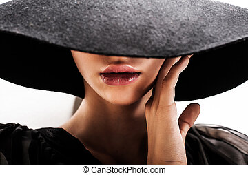 Beautiful woman with full lips in black hat poses on white...