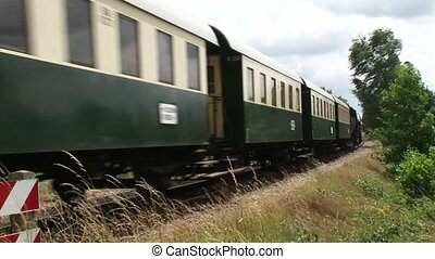 Steam train retro carriages riding in countryside - passing...