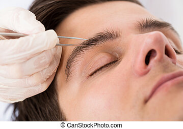Beautician Hands Plucking Man Eyebrows With Tweezers -...
