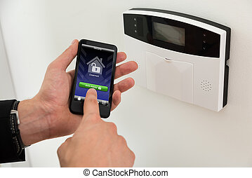 Businessperson Arming Security System - Close-up Of...