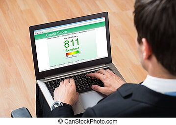 Businessperson Checking Online Credit Score Record On Laptop...