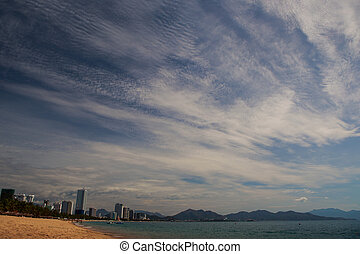 view of strange fleecy and stratus clouds above sea beach -...