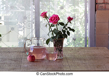 Apple compote in a transparent jug, a bouquet from roses and...