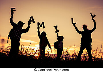 Happy family standing in the field at the sunset time They...