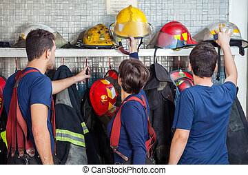 Firefighters Removing Helmets From Shelf - Male and female...