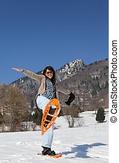 woman with snowshoes in the white snow - beautiful young...