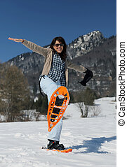 woman with snowshoes in the snow during the winter holidays...