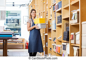 Confident Woman Carrying Boxes In Store - Portrait of...