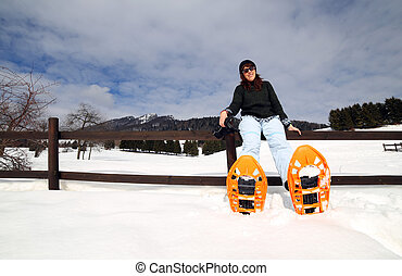 relax of woman with snowshoes in the snow during the winter holidays in the mountains